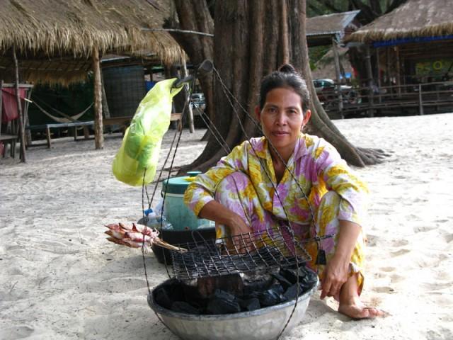 Продавщица жаренных кальмаров на пляже...