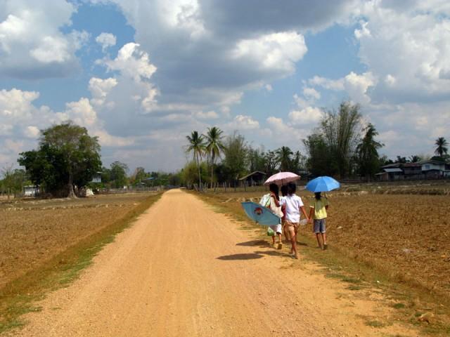 В Лаосе все ходят, и даже ездят на мотоциклах с зонтиками