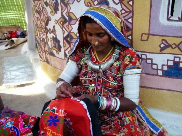 Женщина племени рабари вышивает на пороге своего дома
