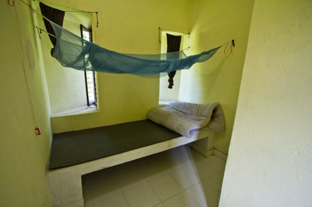 Бетонная кровать, пенка и матрац на ней, висит москитная сетка